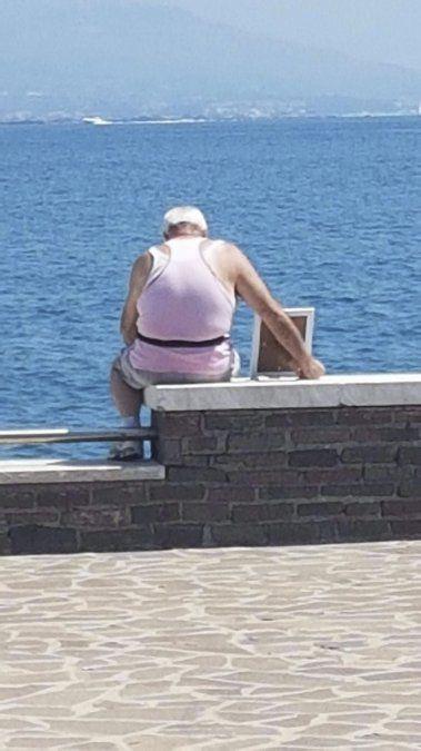 La foto que conmueve a Italia: un hombre frente al mar con el retrato de su esposa