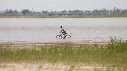En la laguna Setúbal, la bajante amplió la zona de playa y permite que los santafesinos hasta se animen a andar en bicicleta en la orilla.