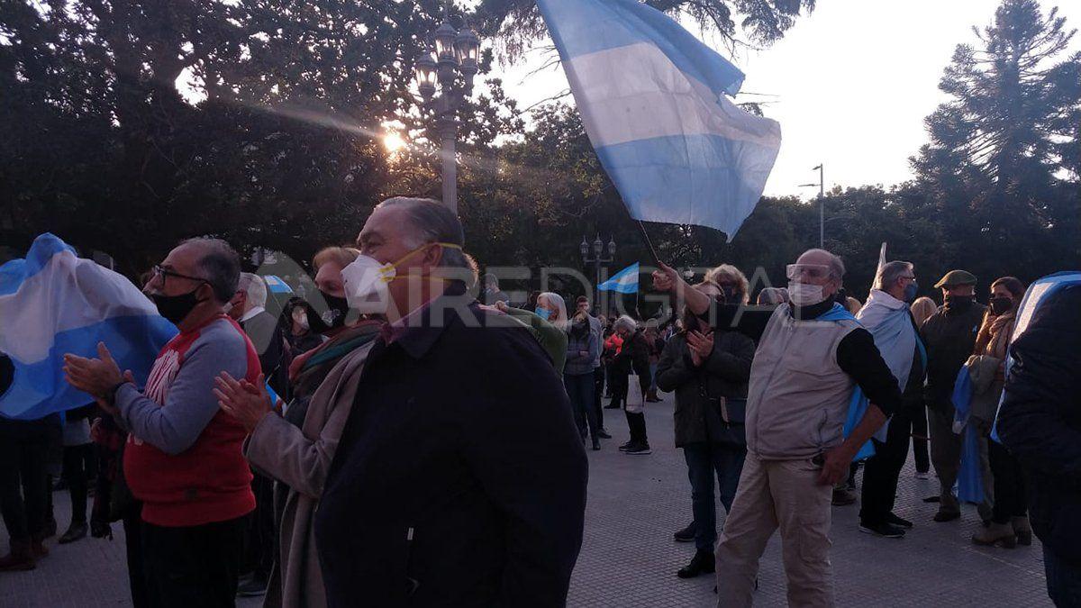 Un hombre levanta una bandera Argentina reclamando por la soberanía de las empresas privadas en Argentina.