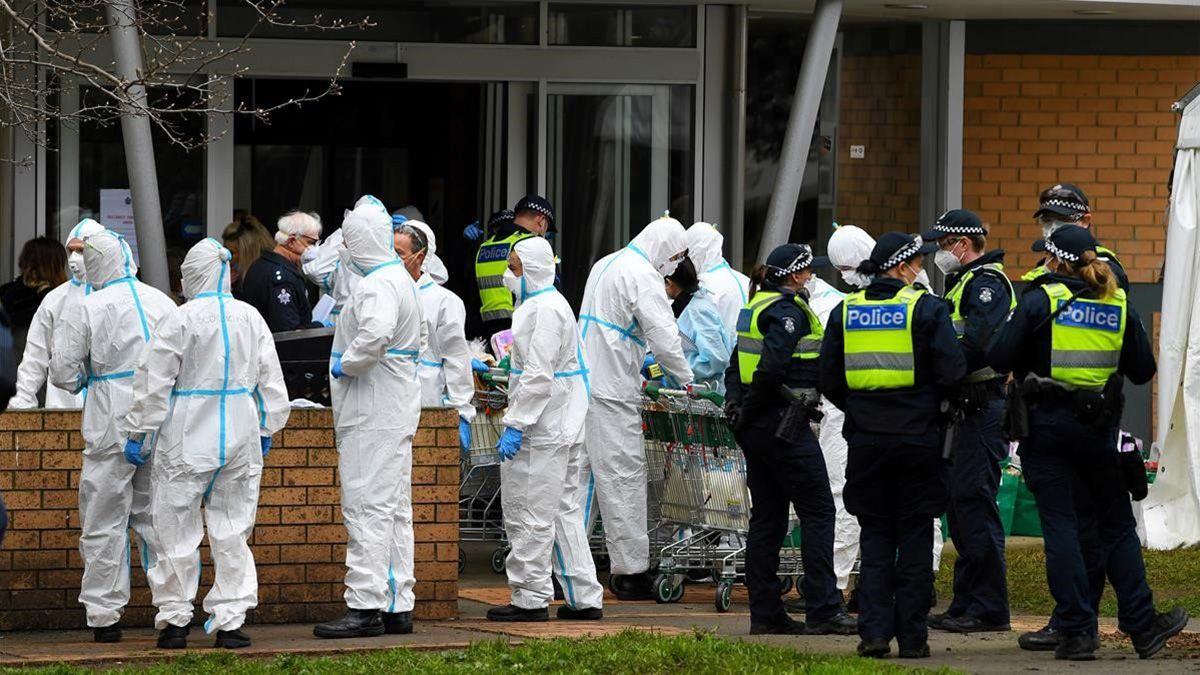 Los bomberos vestidos con equipo de protección personal se preparan para distribuir alimentos en una torre de viviendas públicas en el norte de Melbourne