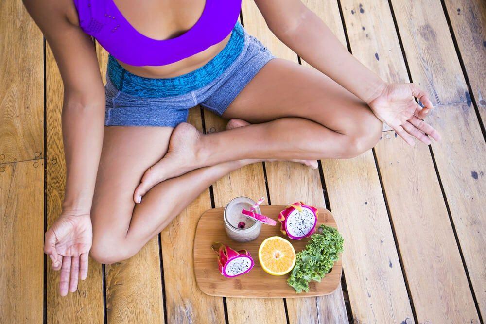 Mujer haciendo yoga con frutas delante.