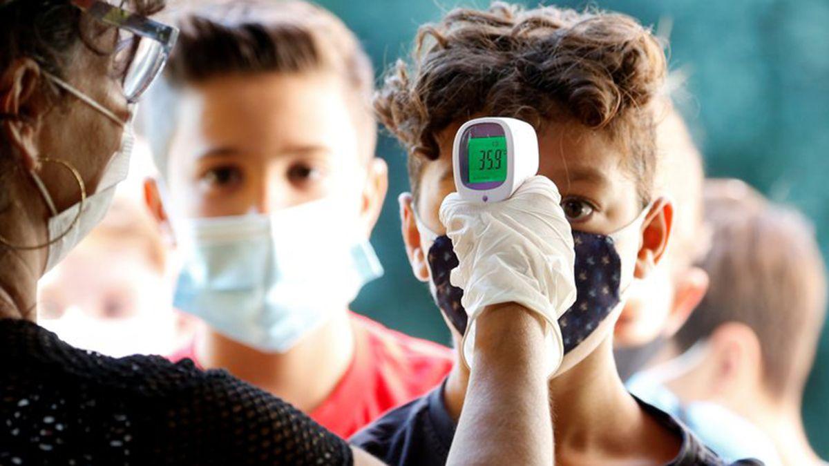 Una maestra le toma la fiebre a un alumno en Italia