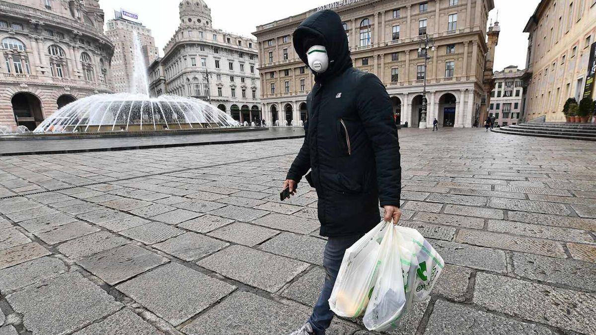 Un ciudadano genovés realiza sus compras cubriendo su cara con un barbijo por la pandemia.