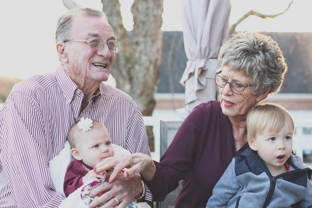 Abuelos riendo y jugando con sus nietos.
