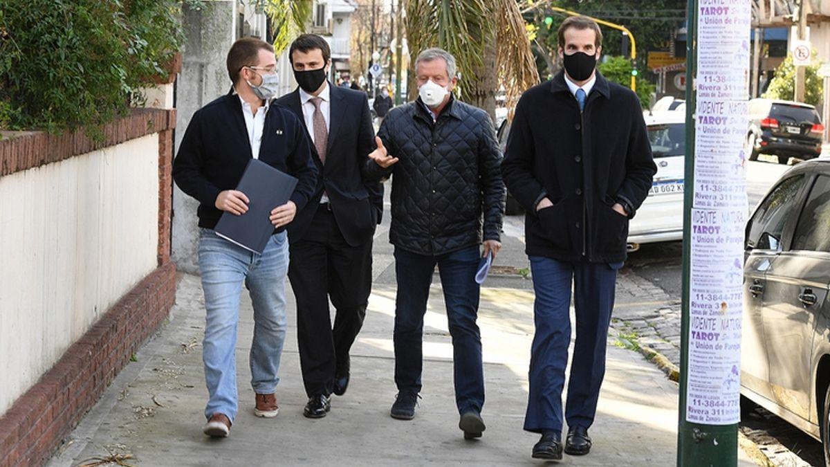 Nicolás Massot (de jeans) junto a Emilio Monzó (barbijo blanco) y sus abogados llegando a los tribunales de Lomas.