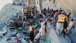 Rescatistas buscan cuerpos de las víctimas tras el accidente de un colectivo por un deslizamiento, con saldo de 16 muertos este domingo 18 de octubre en el norte de Pakistán.