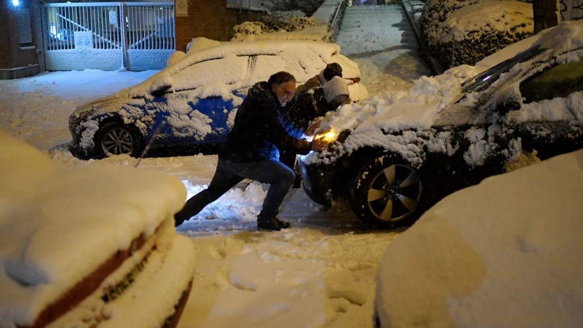 Un hombre intenta mover su auto durante el brutal temporal de nieve en Madrid.