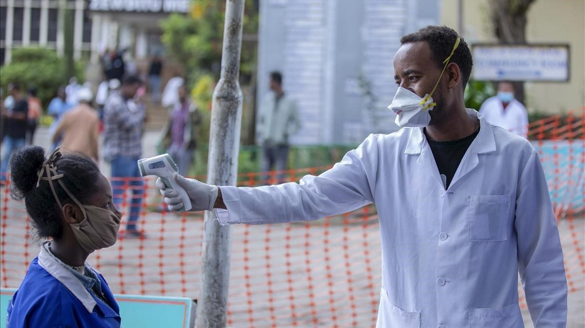 Personal del hospital Zewditu Memorial de Adís Abeba toma la temperatura a una mujer que se dispone aentrar en el centro sanitario.